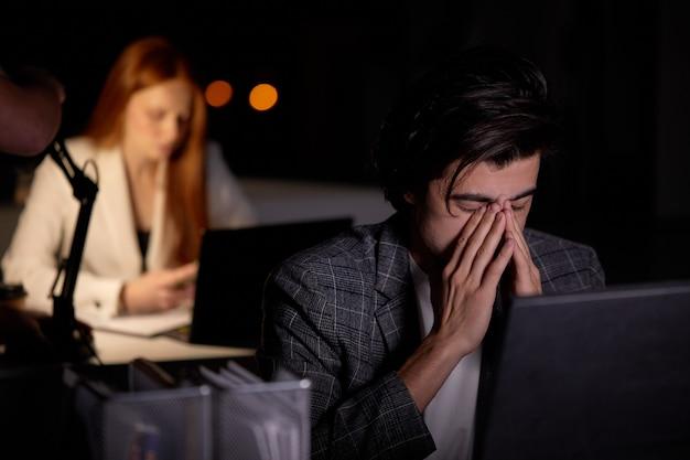 Кавказский бизнесмен выглядит измотанным с головой в руке, работая в одиночестве за столом в офисе поздно ночью, коллега-женщина на заднем плане, фокусируется на мужчине в костюме. бизнес, концепция крайнего срока
