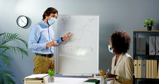Caucasian businessman in medical mask standing at board and explaining formulas and business strategy to african american woman. covid-19 concept. mixed-races male and female talking in office.