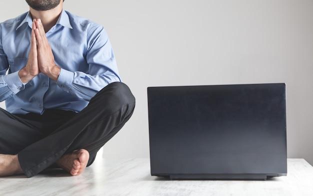 Caucasian businessman meditating in office. lotus position. relax