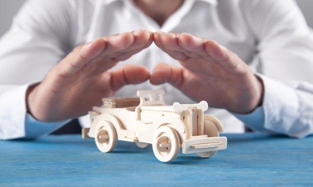 백인 사업가 나무 장난감 자동차를 보호합니다.