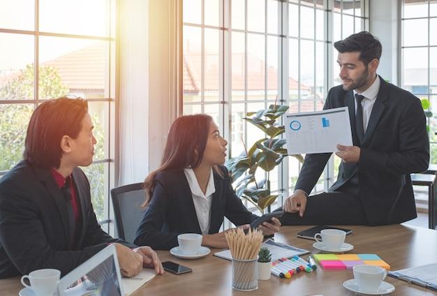 백인 사업가 회의실에서 작업 장소에서 아시아 동료에게 프레젠테이션 차트를 표시합니다.