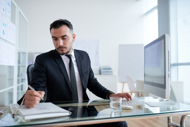 Caucasian businessman sitting at desk in front of computer and writing on document folder