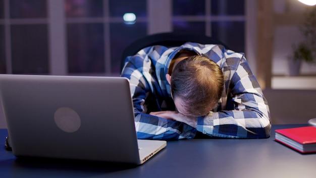 オフィスで頭を抱えて寝ている白人実業家。働き過ぎの起業家。