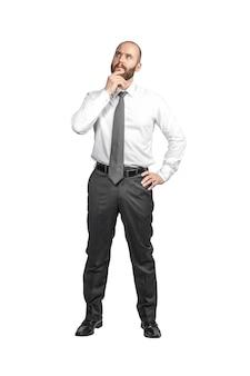 白で隔離の思慮深い表情で立っている白人ビジネスマン。