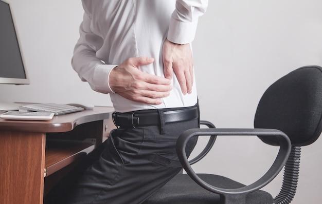 사무실에서 허리 통증으로 고통받는 백인 사업가.