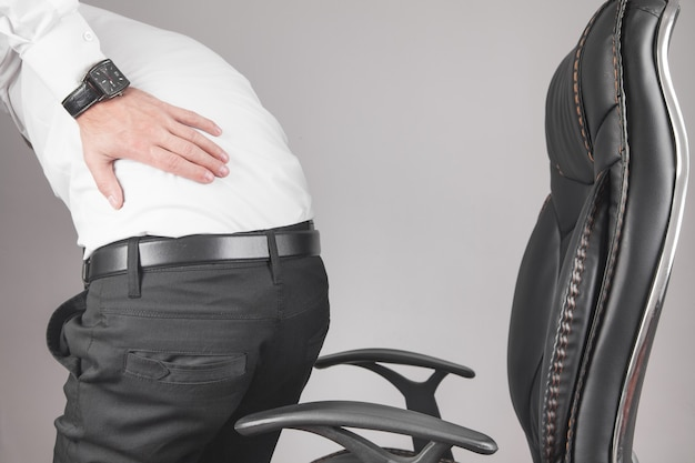 Кавказский бизнесмен страдает от боли в спине в офисе.