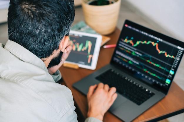 オンラインで取引し、コンピューター技術を使用し、証券取引所の取引を調べ、分析する白人ビジネスマン
