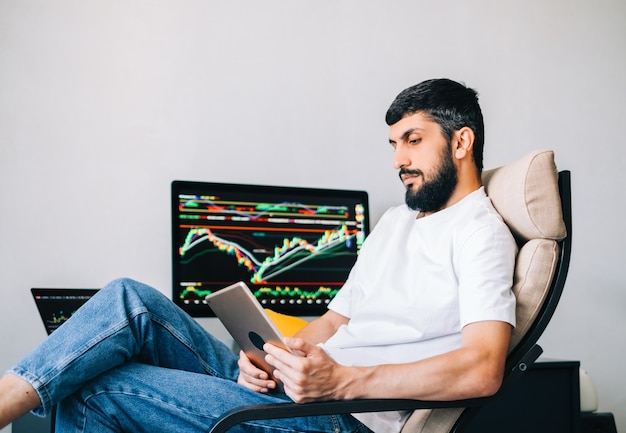 Caucasian businessman trading online, using computer technology, looking on stock exchange trade and analyzing