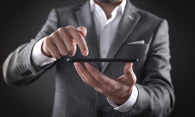 オフィスでスマートフォンを使用して白人ビジネスマン。