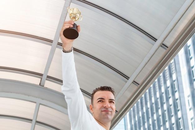 Caucasian businessman wins a trophy.