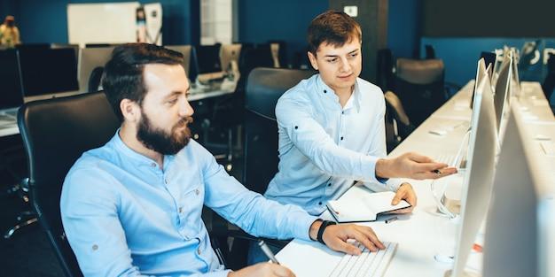 Кавказский бизнесмен с бородой обсуждает со своим коллегой, указывая на компьютер в их офисе
