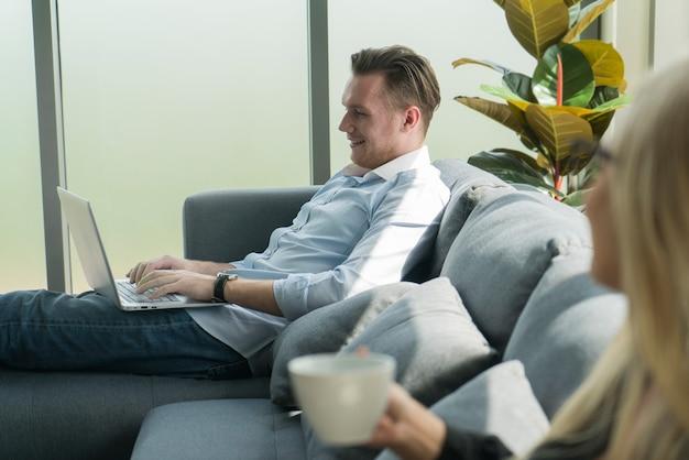 ノートパソコンに取り組んでいる白人ビジネスマンは、自宅で働くためのアパートのアイデアでリラックスして幸せ