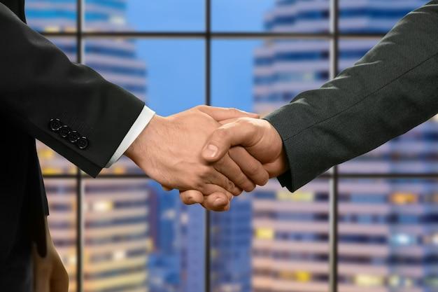 握手する白人ビジネスマン。マネージャーは超高層ビルの横で握手します。仕事で生産的な日。成長と発展。