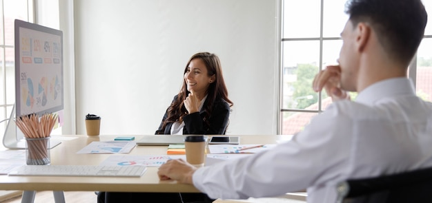 Caucasian businesswoman manager sitting discussing explaining presenting analysis statistic financial data graph chart information report on big computer screen to businessman colleague in office.