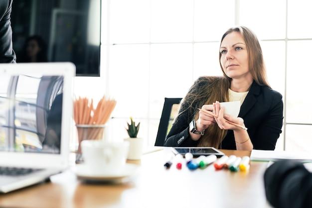 パートナーシップのコンサルティングを聞きながら、カップを持って座っている白人実業家