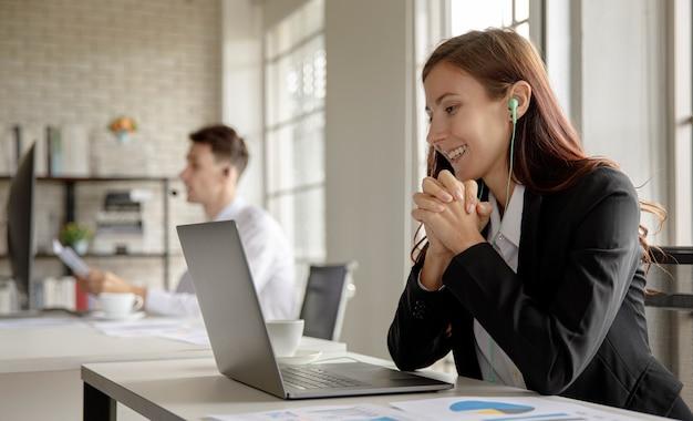 白人実業家スタッフ従業員労働者ホットラインヘルプラインオペレーターは、正式なビジネススーツを着て、クライアントと顧客とのビデオ通話電話会議での会議について話し合って座ってイヤホンを着用します。