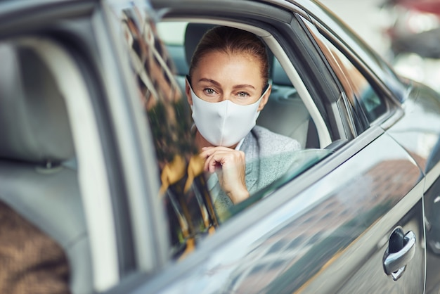 Caucasian businesswoman wearing medical protective mask sitting on back seat in the car and looking
