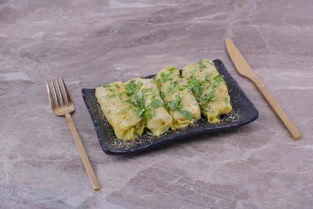 Impacchi di cavolo caucasico con erbe tritate in un piatto di ceramica nera.