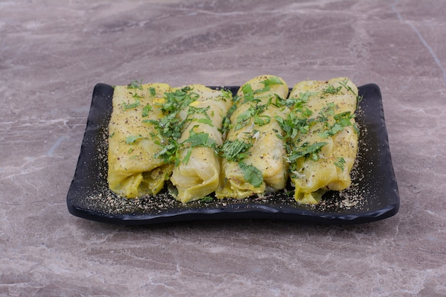 Завитушки из кавказской капусты с рубленой зеленью на черном керамическом блюде.