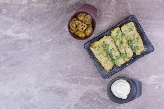 백인 양배추는 요구르트와 절인 야채와 함께 검은 접시에 먹거리로 포장합니다.