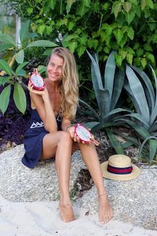 La donna felice calma caucasica in vestito blu tiene la frutta del drago sulla spiaggia tropicale