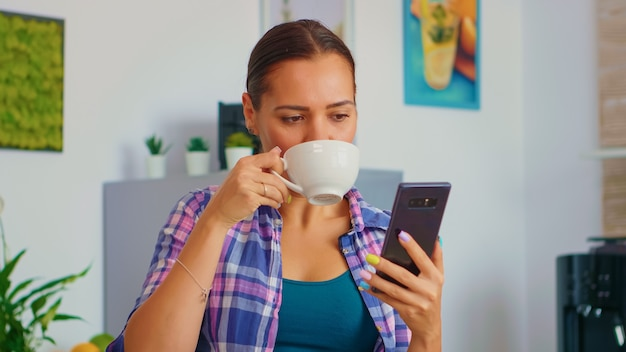 スマートフォンでスクロールし、朝食時に緑茶を飲む白人の陽気な女性。インターネット技術のブラウジングを使用してタッチスクリーンで電話デバイスを保持し、ガジェットで検索します。