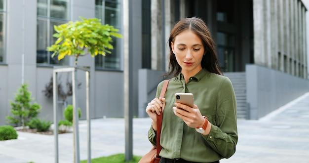 通りでスマートフォンをタップまたはスクロールする白人の陽気な若いスタイリッシュな女性。携帯電話で美しい幸せな女性のテキストメッセージ。外側。携帯電話でsmsを送信します。