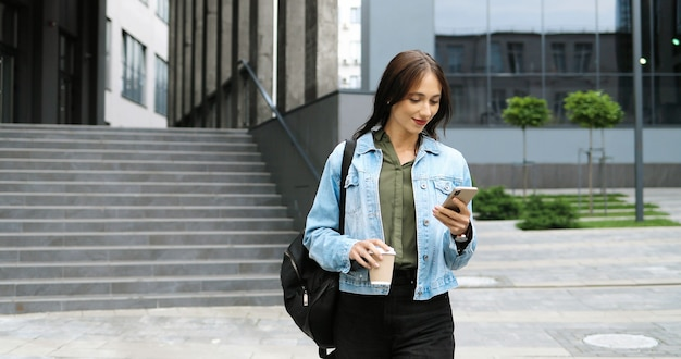 Caucasian cheerful young stylish woman walking the street, tapping or scrolling on smartphone and sipping hot drink in the morning. beautiful happy female texting message on phone and drinking coffee.