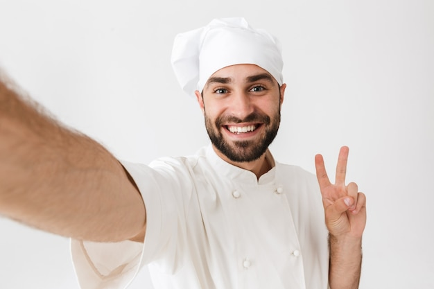 Caucasian chef man in cook hat showing peace sign and smiling while taking selfie photo at work isolated over white wall