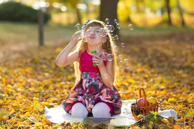 Caucasian child girl blowing soap bubbles outdoor at autumn sunset