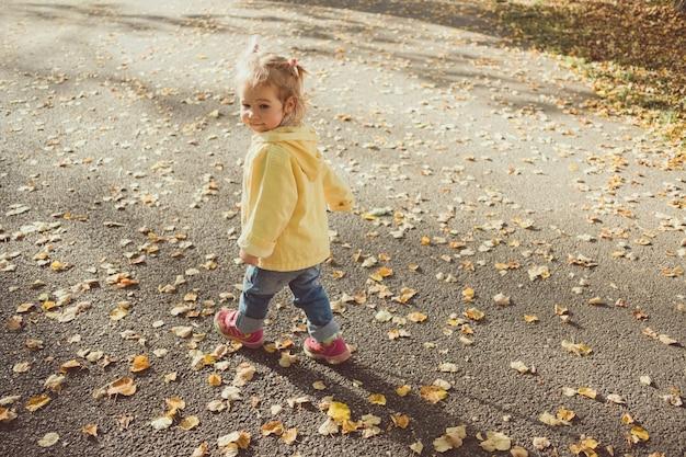 Кавказская детская девочка, одетая в куртку, гуляет в парке осенью.