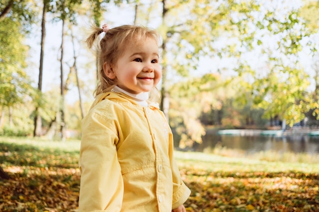 Кавказская детская девочка, одетая в куртку, гуляет в парке.