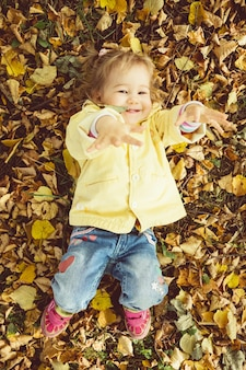 Caucasian child girl dressed in a jacket lies on the ground in autumn leaves.