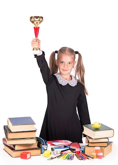Кавказская девочка держит кубок и медаль на белой поверхности