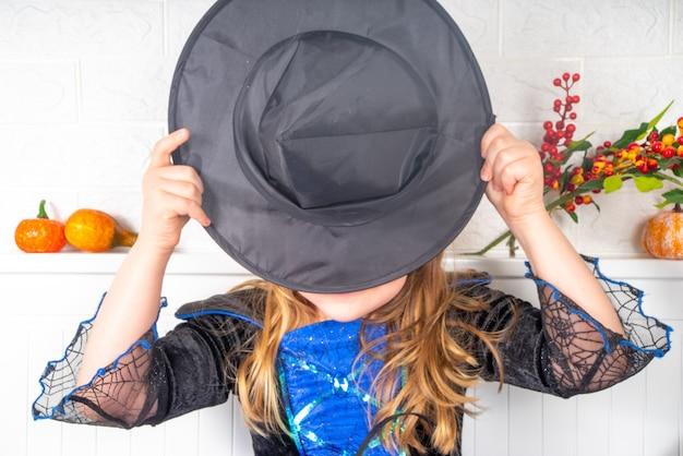 Кавказская девочка в платье и шляпе ведьмы дома