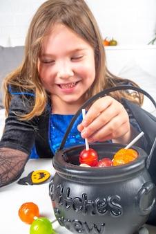Кавказская девочка в платье и шляпе ведьмы, с ведрами конфет дома копией пространства
