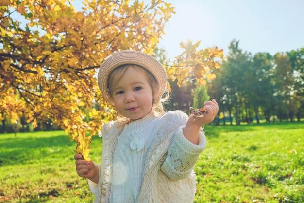 Кавказская девочка в деревенской одежде гуляет в шляпе осенью в парке.