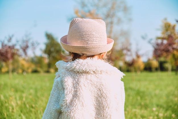 Кавказская девочка в деревенской одежде гуляет спиной в осеннем парке.