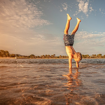 Caucasian child plays the vertical in the sea where the water is low
