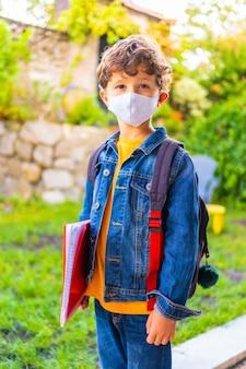 学校に戻る準備ができてフェイスマスクを持つ白人の子。新しい正常性、社会的距離、コロナウイルスのパンデミック、covid-19。ジャケット、バックパック、手元のメモ用の赤いブロック