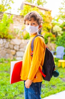 学校に戻る準備ができてフェイスマスクを持つ白人の子。新しい正常性、社会的距離、コロナウイルスのパンデミック、covid-19。オレンジ色のtシャツ、バックパック、メモ帳を手に