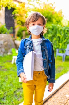 学校に戻る準備ができてフェイスマスクを持つ白人の子。新しい正常性、社会的距離、コロナウイルスのパンデミック、covid-19。デニムジャケット、バックパック、メモ帳を手に