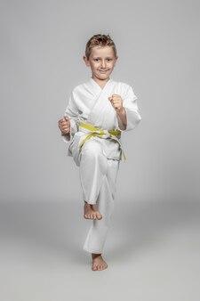 Caucasian child with kimono practices kata