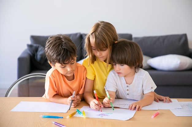 Caucasian children painting with markers in living room. cute little boys and blonde girl sitting at table together, drawing on paper and playing at home. childhood, creativity and weekend concept
