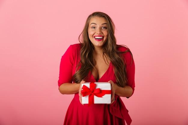 백인 통통한 여자 20 대 빨간 드레스를 입고 웃고 선물 상자를 들고