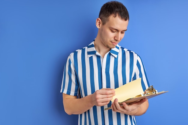 論文文書読書ノートをクリップボードでポーズをとる白人集中男性