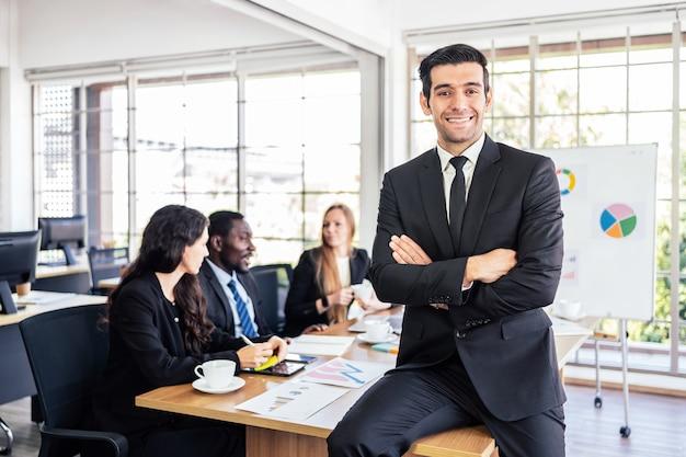 백인 자신감 사업가 회의 테이블에 앉아 좋은 분위기에서 미소.