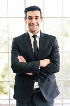 カメラを見て、良い気分で笑顔のスーツを着ている白人の自信を持ってビジネスマン