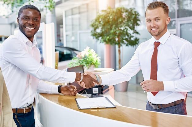 白人コンサルタントの男がアフリカ系アメリカ人のcutomer男に握手をします