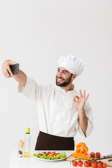 Caucasian cook man in uniform showing ok sign and taking selfie photo of food on smartphone at work isolated over white wall